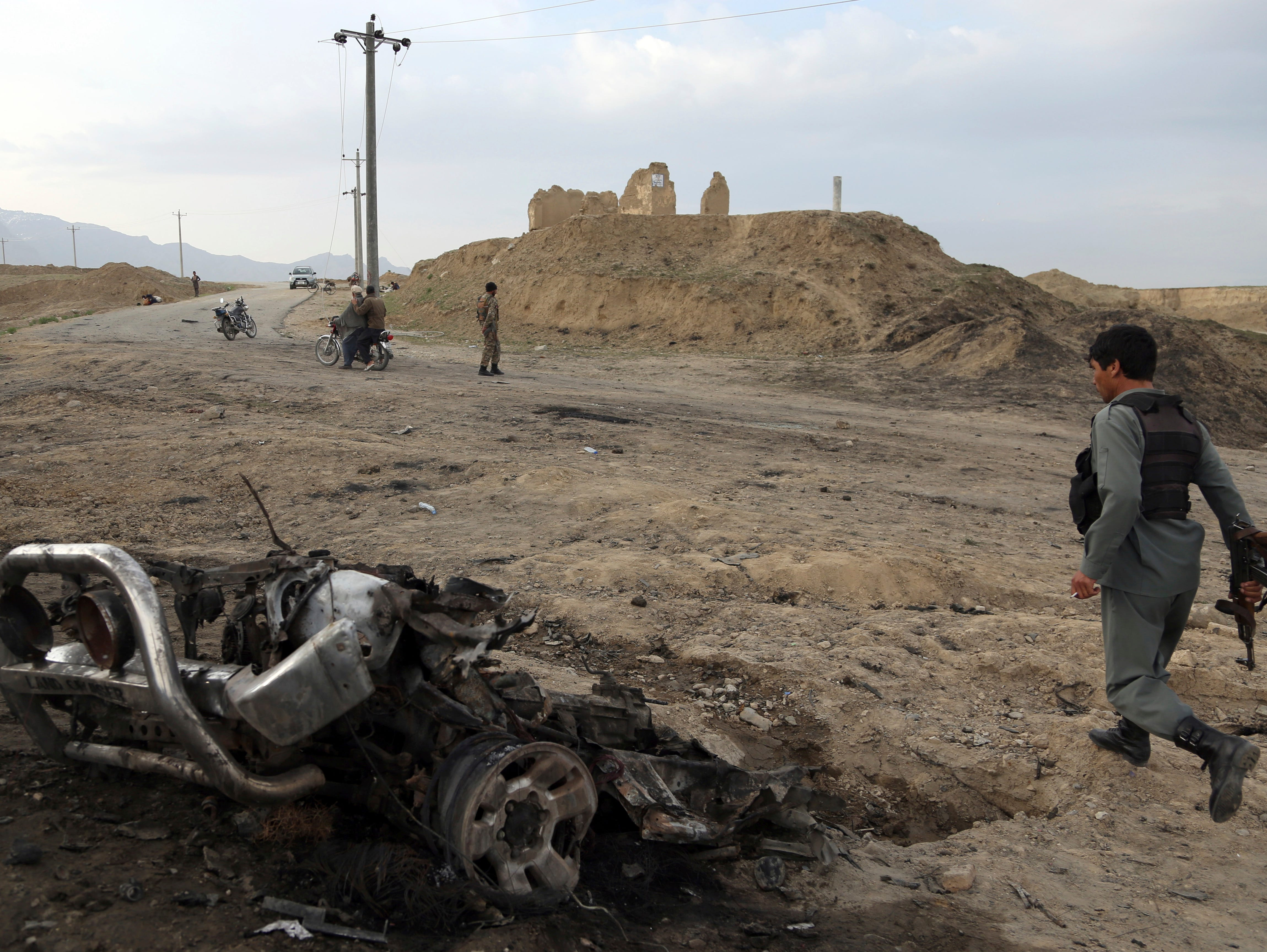 Afghan security forces gather at the site of Monday's attack near the Bagram Air Base, north of Kabul, Afghanistan, Tuesday, April 9, 2019. Three American service members killed when their convoy hit a roadside bomb on Monday near the main U.S. base in Afghanistan, the U.S. forces said. The Taliban claimed responsibility for the attack.