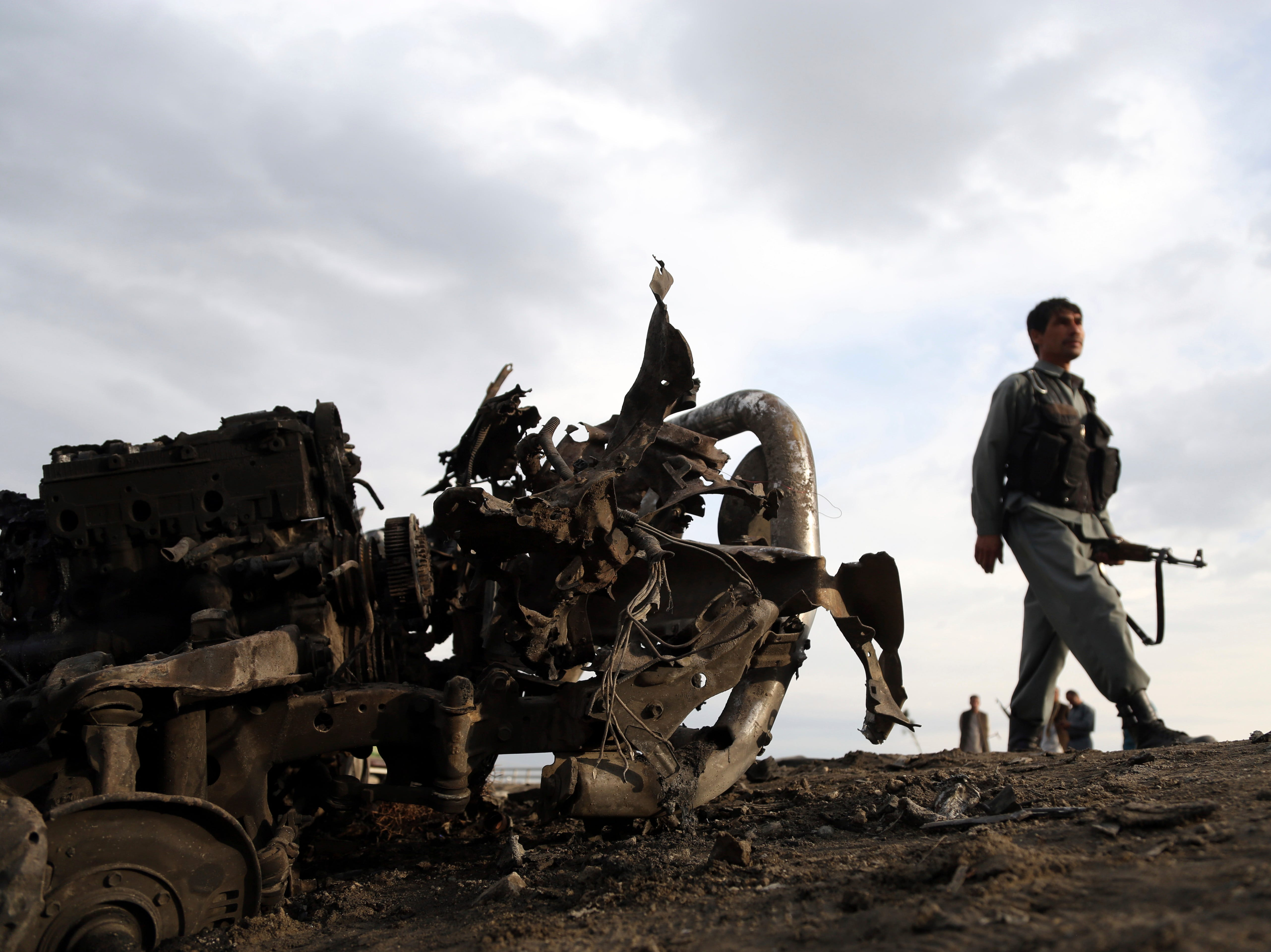 Afghan security forces gather at the site of Monday's attack near the Bagram Air Base, north of Kabul, Afghanistan, Tuesday, April 9, 2019. Three American service members were killed when their convoy hit a roadside bomb on Monday near the main U.S. base in Afghanistan, the U.S. forces said. The Taliban claimed responsibility for the attack.