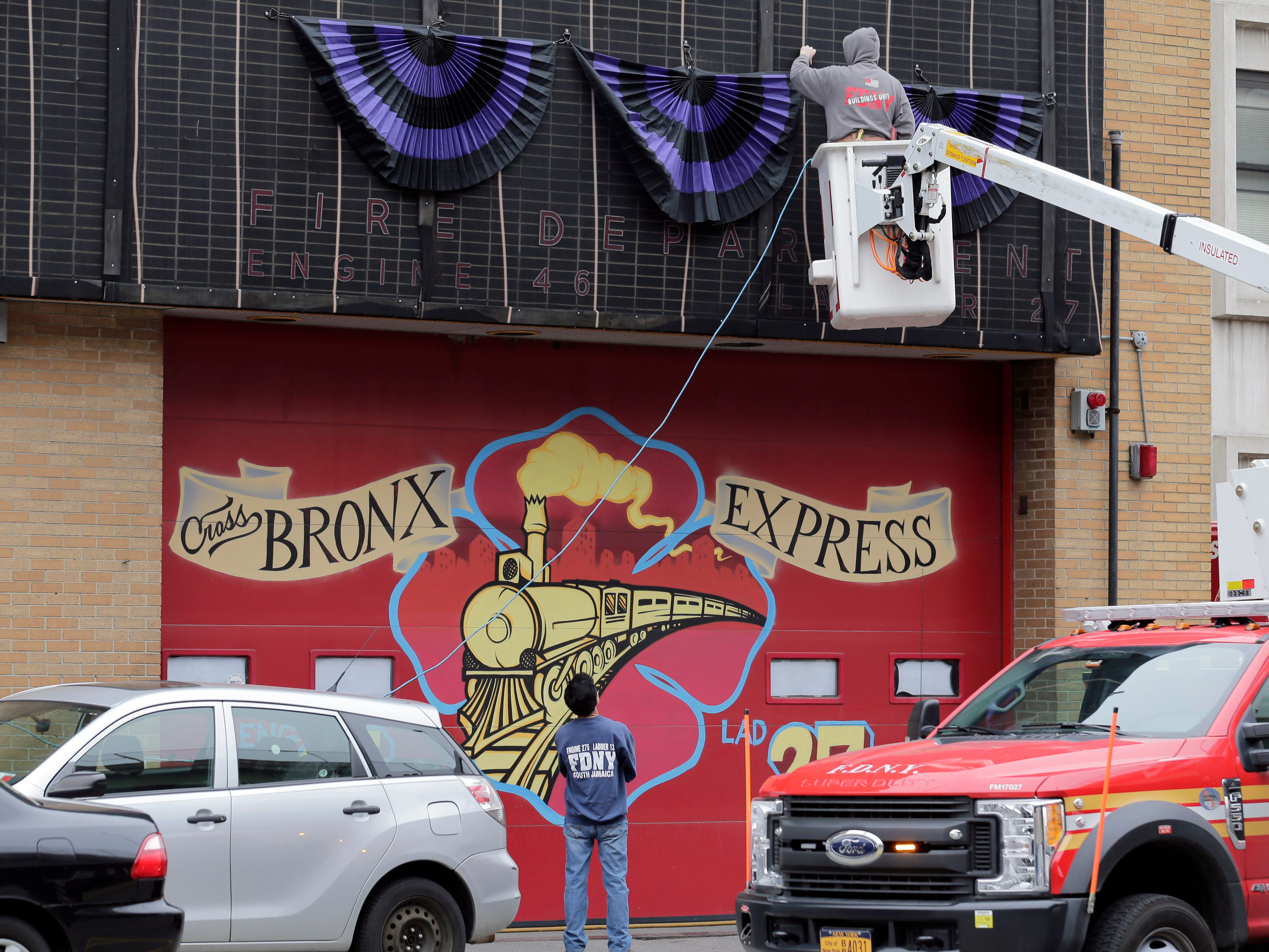 A firefighter hangs bunting over a firehouse in the Bronx borough of New York, Tuesday, April 9, 2019.   Christopher Slutman, a 15-year FDNY member, was among three American service members killed by a roadside bomb in Afghanistan on Monday.  New York City said Slutman was the fourth FDNY member to die while serving in Iraq or Afghanistan since 2003.
