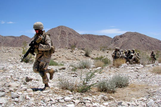 June 30, 2008 photo shows Lance Cpl. Christopher Slutman as he rushed across a danger area with his platoon through a grueling fire and maneuver course in California.