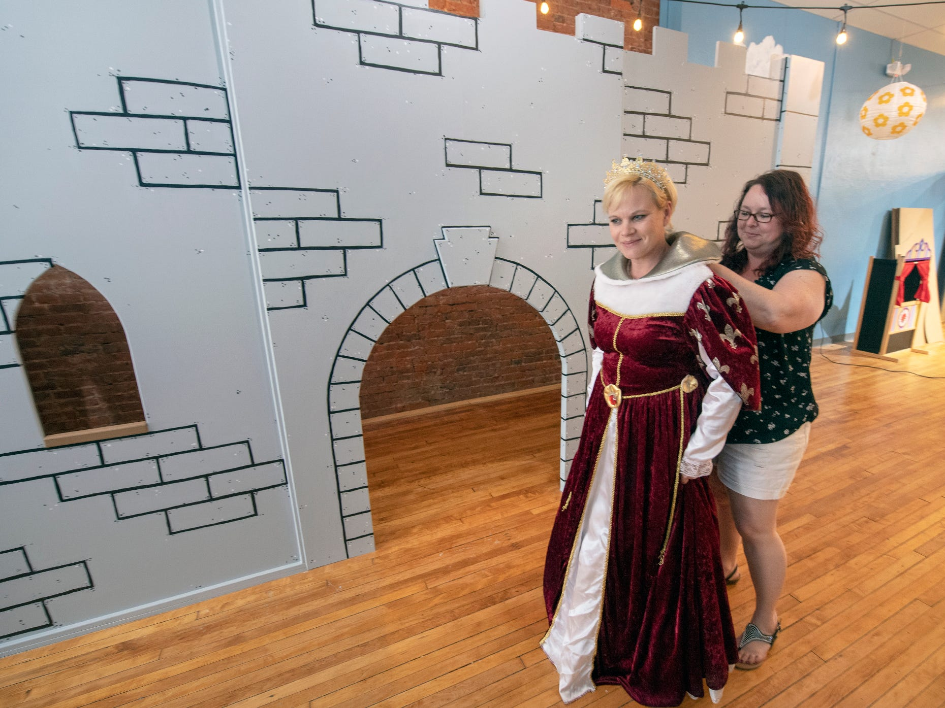 Owner Jen Swanner, right, helps manager Heidi Wildasin try on her queen costume at The Curious Little Playhouse in York.