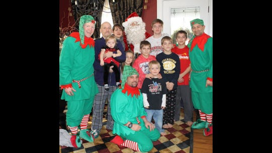 "Lou Lombardo, dressed as Santa Claus, visiting the Kropman family in Penfield years ago with ""elves"" Penfield coach John Leone, far left, Webster Thomas coach Neil Cook, center, and Penfield assistant coach Ed Porto."