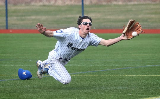 Webster Schroeder right fielder Alex Vogt dives but can't make the catch on a double down the line by Victor's Hudson Alread in the second inning during their Section V matchup April 8 at the Basket Road Field in Webster. Victor won the game 8-6.