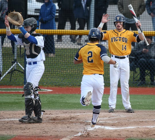 Victor's Santino Rosso, center, races home and toward celebrating teammate Hudson Alread after scoring on a double by teammate CJ Williams in the fourth inning. At left is Schroeder catcher Matt Piccarreto.