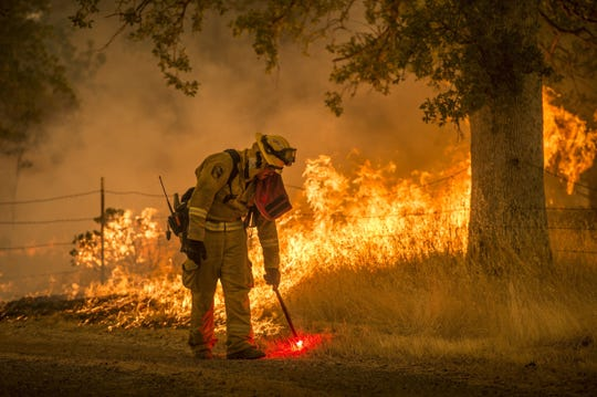 A Cal Fire firefighter creates a back burn on Cloverdale Road near Redding on Saturday, July 28, 2018 during the Carr Fire.