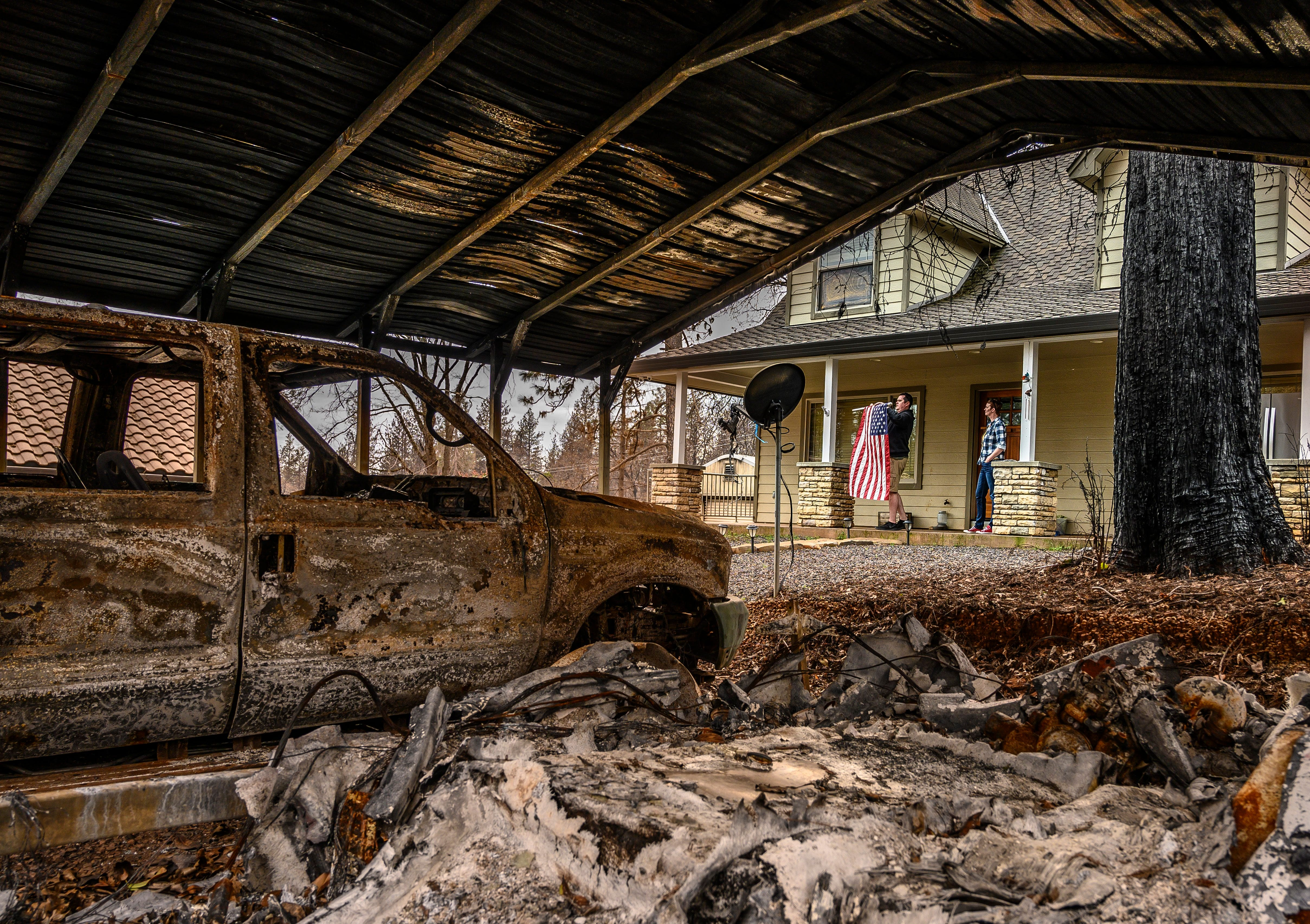 Sean and Dawn Herr collect an American flag on Tuesday, March 19, 2019, that survived the Camp Fire – along with their Paradise home. A shed containing the family vehicle and a boat burned, along with nearby homes. The Herr's home was built in 2010, and the family credits its survival to its construction features and their attention to defensible space.