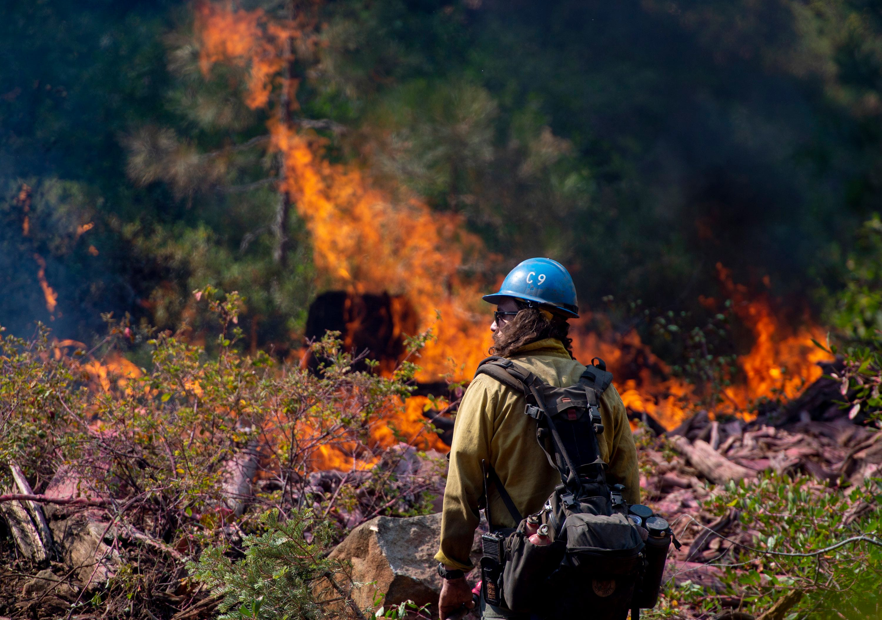 Tyler Medders of the Susanville Hot Shots keeps an eye out for embers at the North Fire near the North Fork Campgrounds in Placer County on Tuesday, September 4, 2018.