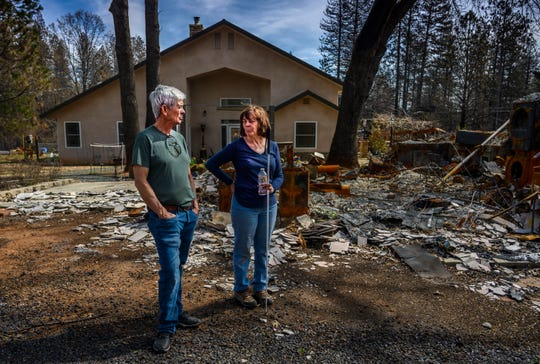 Oney and Donna Carrell stand near the ashes of her father's house on Tuesday, March 19, 2019, in Paradise. Their property had two homes on it before the fire, but the only one to survive – visible behind them – was built to fire-resistant standards that went into effect in 2008.