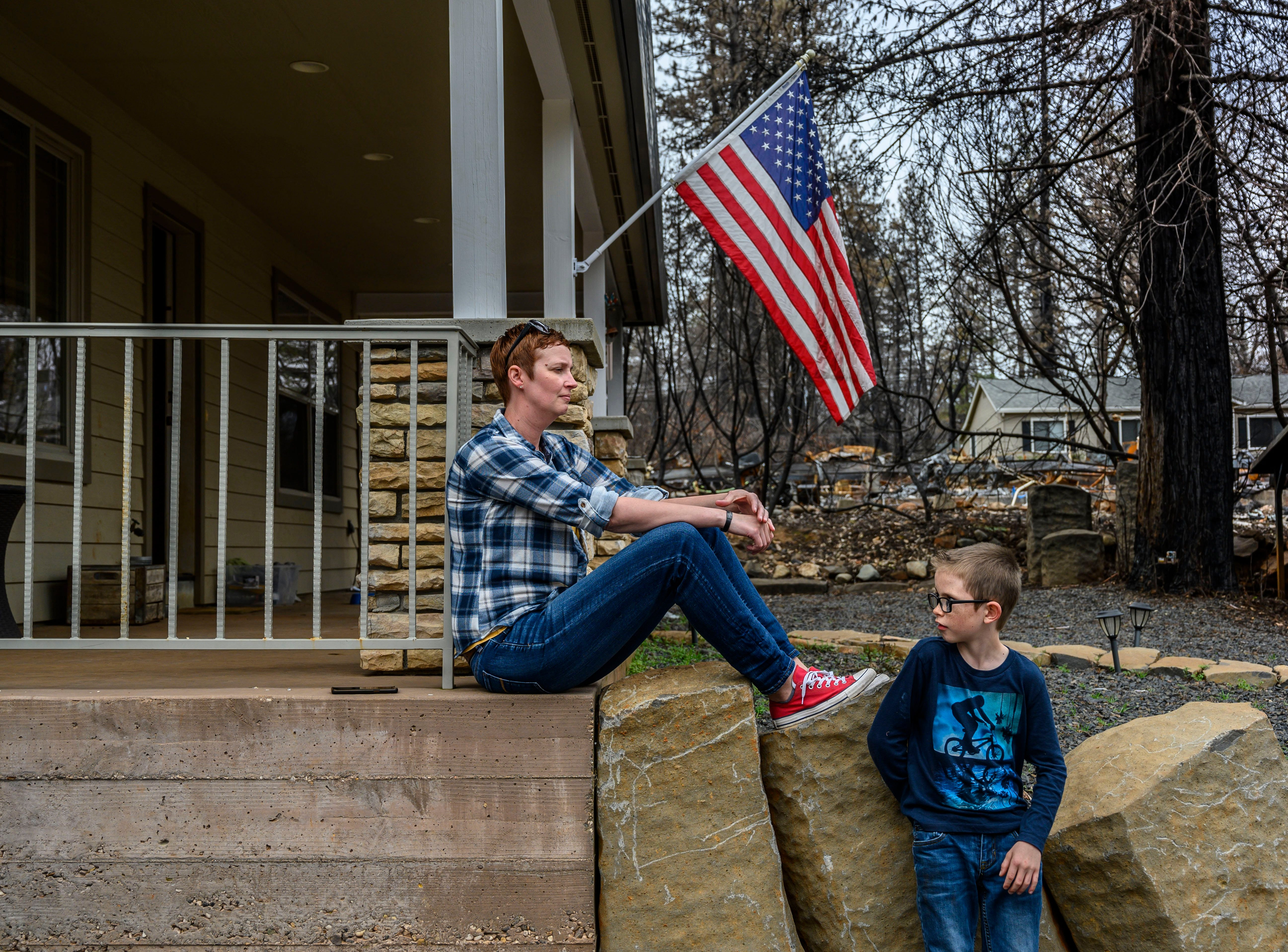 Dawn Herr and her son Liam, 8, visit their home on Tuesday, March 19, 2019 in Paradise that survived the Camp Fire.