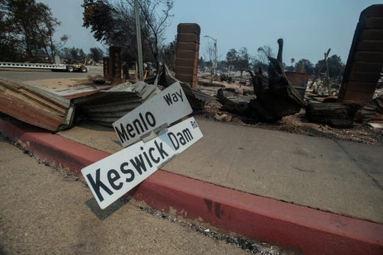 A sign indicating the intersection of Keswick Dam Rd. and Menlo Way lays on the sidewalk on Keswick Dam Rd. in Redding, Friday, July 27, 2018.