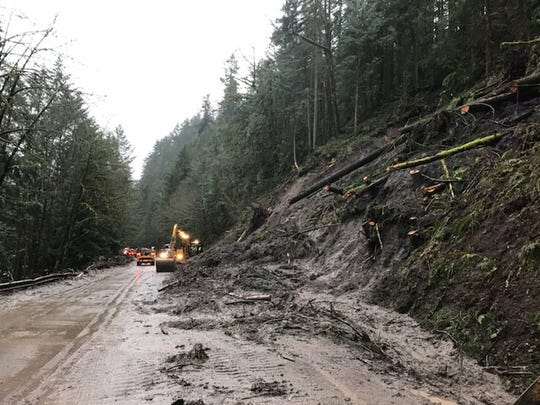 Crews work to open a lane on Highway 58 near Oakridge following a landslide.