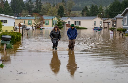 Shannon Archuleta, left, and her son Jett Archuleta wade through a flooded street in the Riverstone Mobile Home Park in Cottage Grove, Ore., Monday, April 8, 2019, to check on a family member after floodwaters rose overnight.