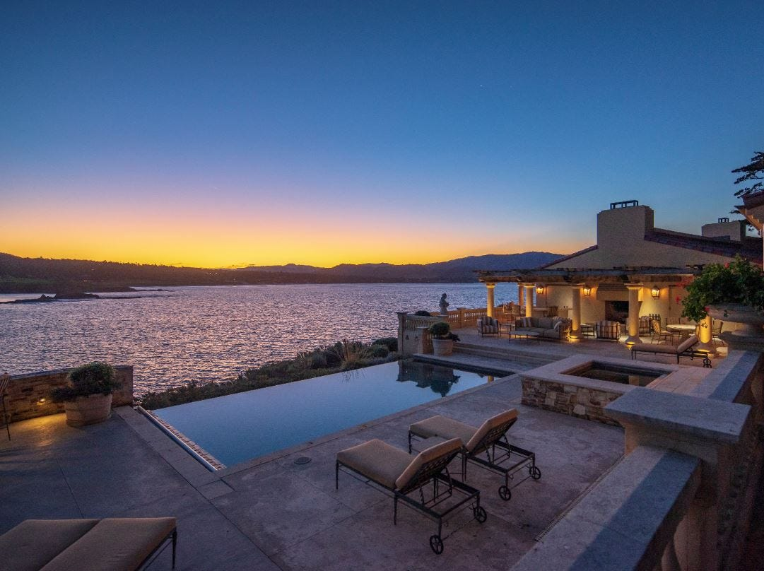 An informal family room leads to a generous waterfront entertainer's terrace, complete with an outdoor kitchen and zero-edge infinity pool with a view of the bay.
