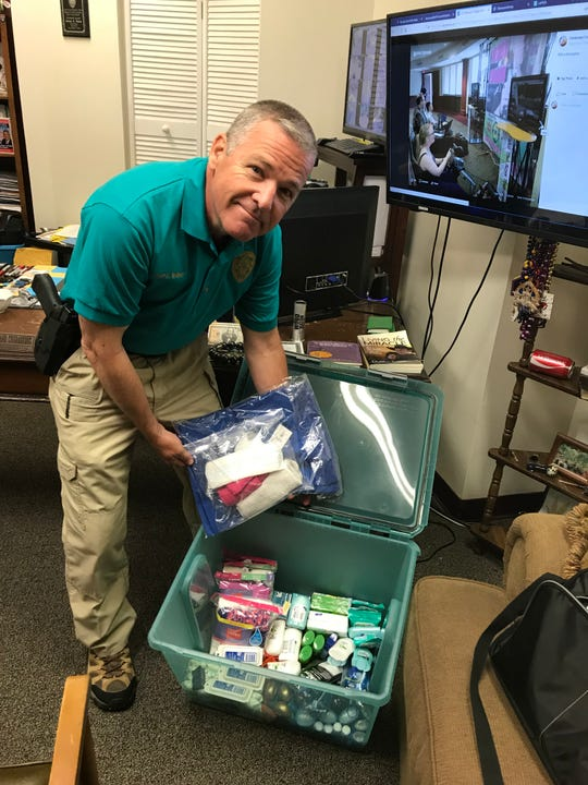 The Police Chief of Centenary College's Department of Pubic Safety poses with the items being collected for a sexual assault advocacy organization in Shreveport.