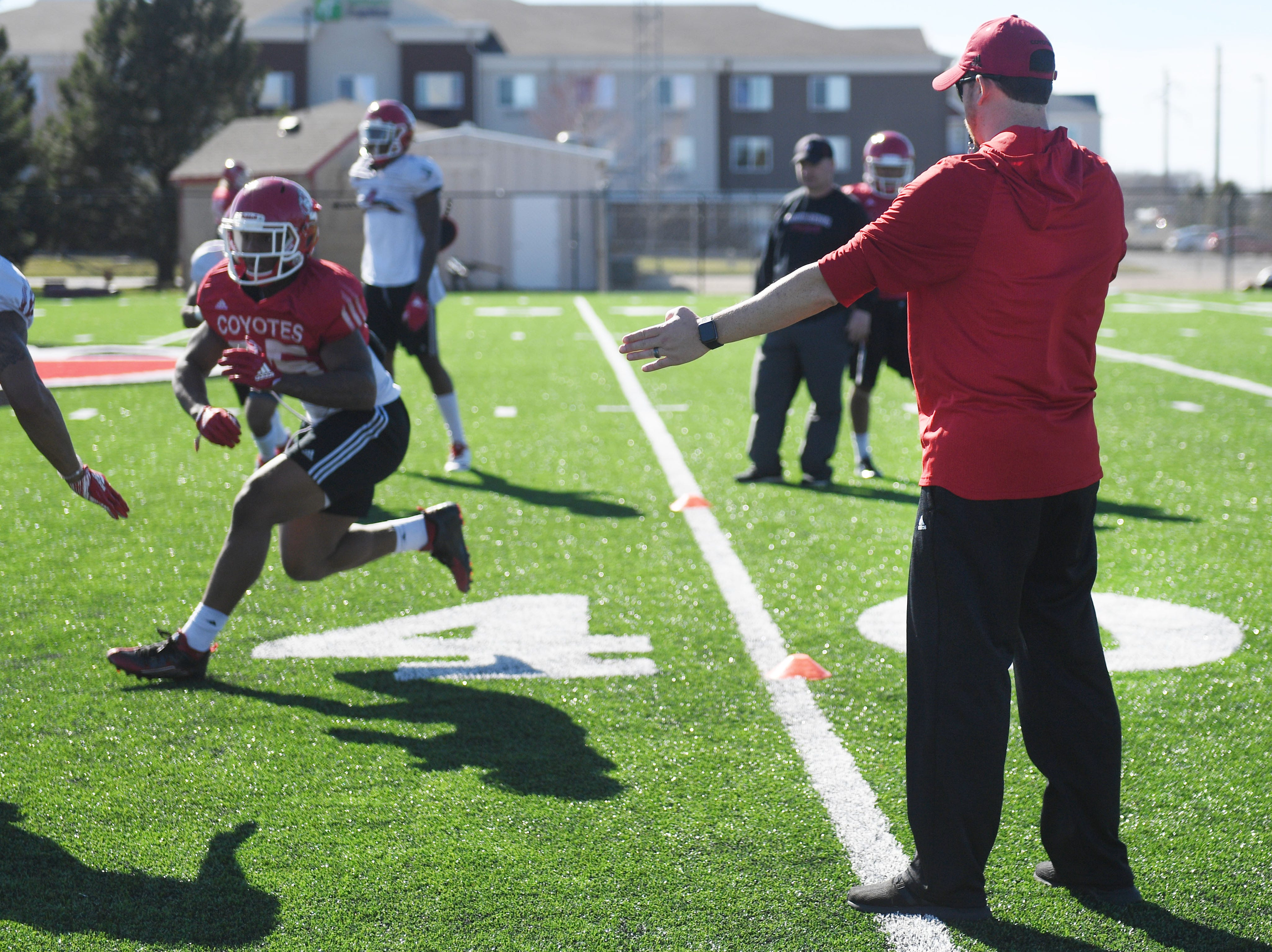 USD coach Travis Johansen, right, during spring football camp Monday, April, 8, on the outdoor practice field at the university in Vermillion.