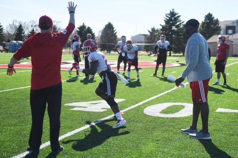 USD coaches Travis Johansen, left, and Abdul Hodge, right, during spring football camp Monday, April, 8, on the outdoor practice field at the university in Vermillion.