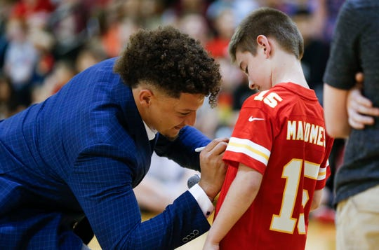 Patrick Mahomes II signs an autograph for a child at the Boys & Girls Clubs of Springfield on Tuesday, April 9, 2019.