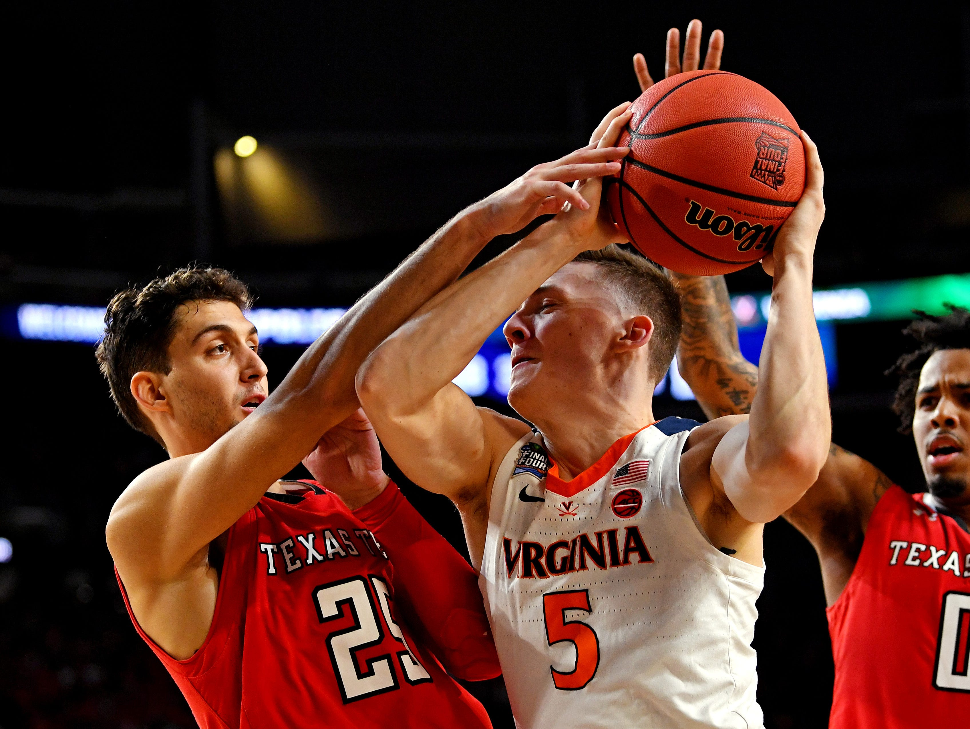 Apr 8, 2019; Minneapolis, MN, USA; Virginia Cavaliers guard Kyle Guy (5) drives to the basket against Texas Tech Red Raiders guard Davide Moretti (25) and guard Kyler Edwards (0) during the first half in the championship game of the 2019 men's Final Four at US Bank Stadium. Mandatory Credit: Bob Donnan-USA TODAY Sports