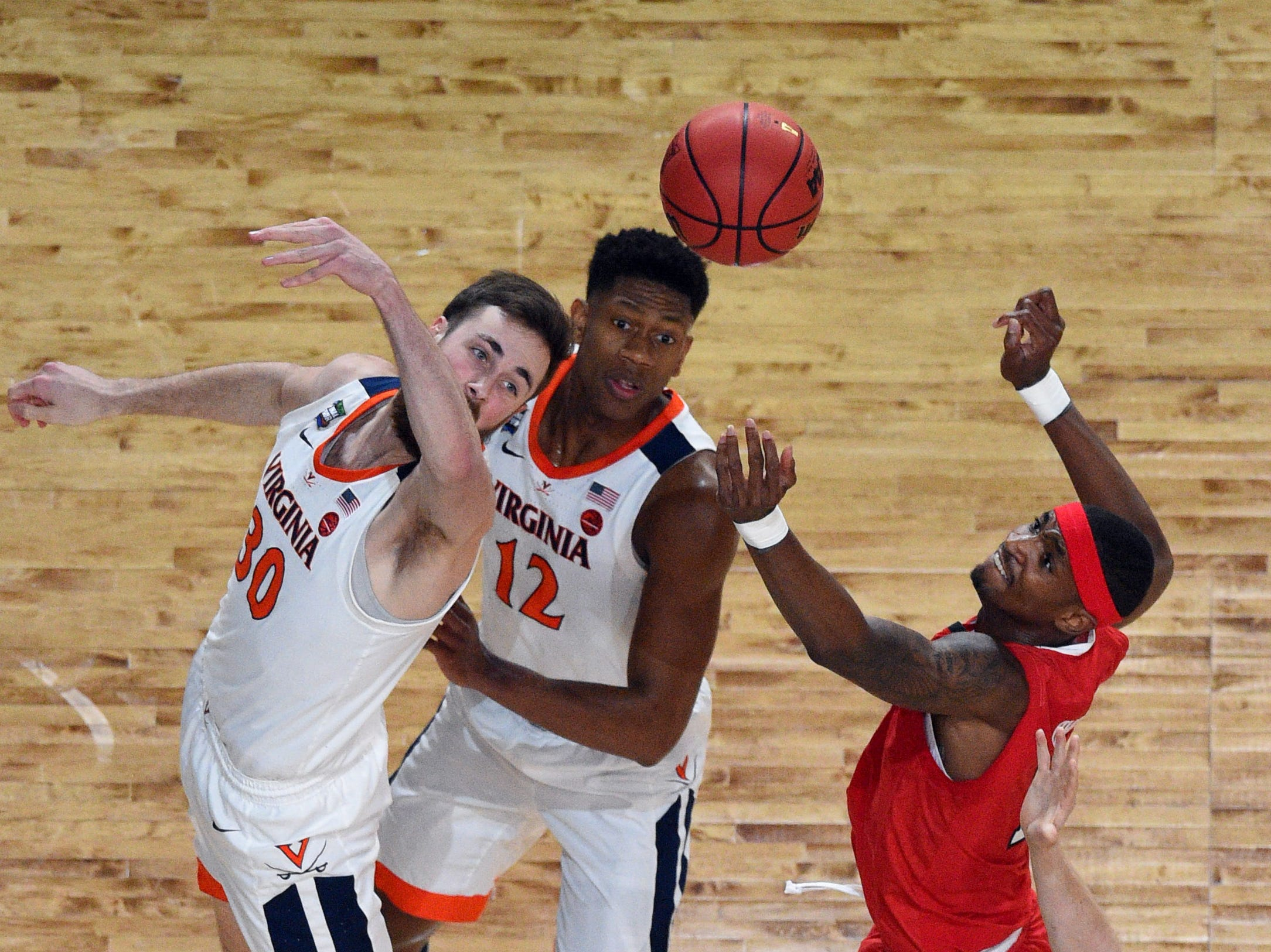 Apr 8, 2019; Minneapolis, MN, USA; Texas Tech Red Raiders forward Tariq Owens (11) reaches for a rebound against Virginia Cavaliers forward Jay Huff (30) and guard De'Andre Hunter (12) in the first half in the championship game of the 2019 men's Final Four at US Bank Stadium. Mandatory Credit: Robert Deutsch-USA TODAY Sports