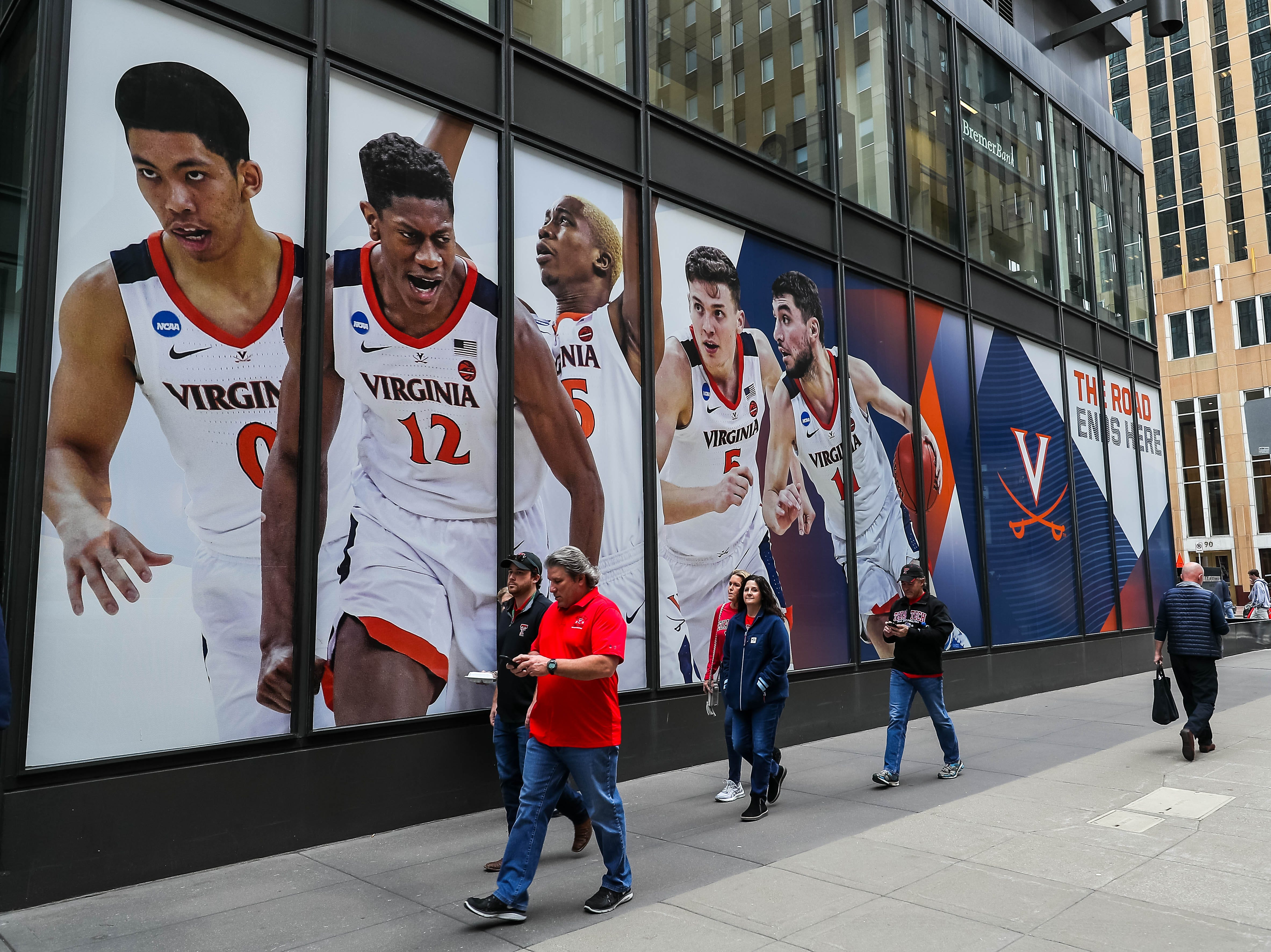 Apr 8, 2019; Minneapolis, MN, USA; Basketball fans walk past a Virginia Cavaliers banner outside before the championship game against the Texas Tech Red Raiders. Mandatory Credit: Brace Hemmelgarn-USA TODAY Sports