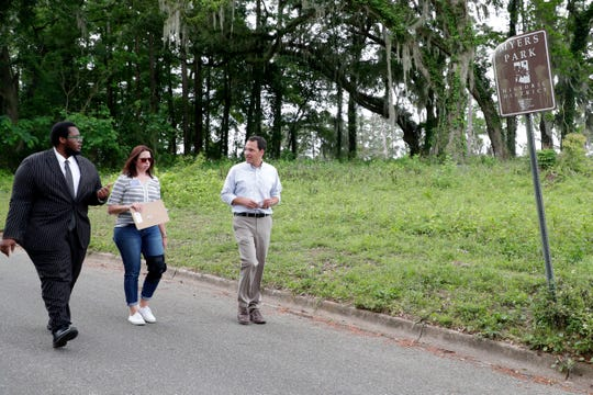 Delaitre Hollinger, an activist, left, Barbara Clark, the historian for the Capital City Country Club, and Jonathan Lammers, a historical preservation consultant, as they walk away from the location of a burial site is believed to be at the Capital City Country Club Tuesday, April 9, 2019.