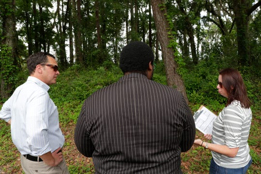 Jonathan Lammers, a historical preservation consultant, left, Delaitre Hollinger, an activist, and Barbara Clark, the historian for the Capital City Country Club, discuss the location of a burial site is believed to be at the Capital City Country Club Tuesday, April 9, 2019.