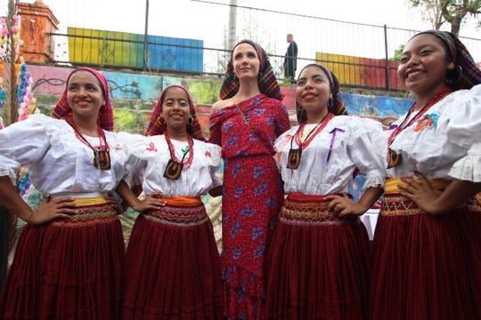 The California governor's wife, Jennifer Siebel Newsom, poses for pictures accompanied by dance students dressed in the traditional costumes that the women of Panchimalco wore a century ago in El Salvador on Monday.