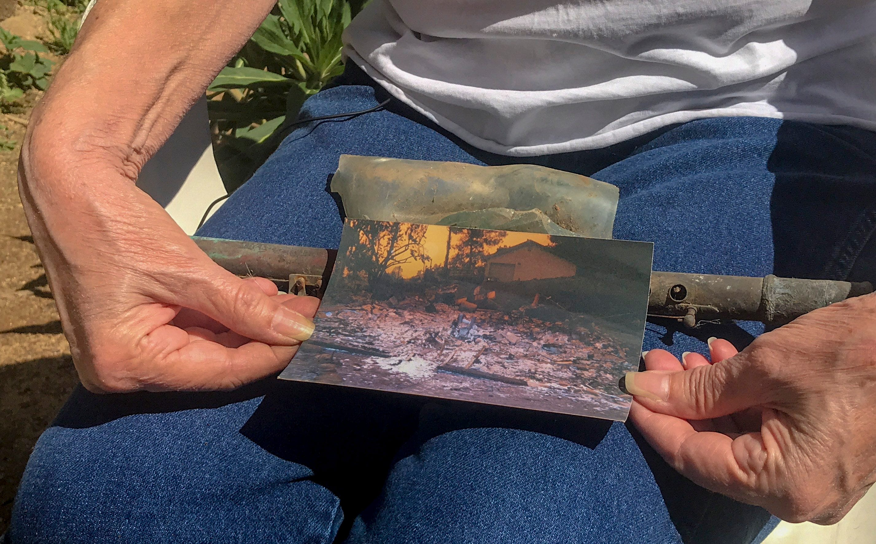 Cheri Skipper, a Harbison Canyon resident, holds her burned flute and a picture showing what her home looked like after it burned during the Cedar Fire in 2003.
