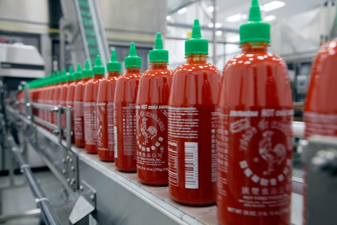 Sriracha bottles emblazoned with a rooster logo are produced at Huy Fong Food's Irwindale plant in this 2013 file photo. The sauce company is suing, and being sued by, Underwood Ranches of Camarillo.