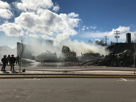 Rainbow Coin Laundry and Blossoms and Bows flower shop in Wausau are torn down Tuesday after a fire earlier that morning destroyed their shared building.