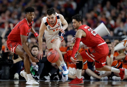 Virginia's Ty Jerome (11) drives between Texas Tech's Jarrett Culver (23) and Davide Moretti (25) during the second half in the championship of the Final Four NCAA college basketball tournament, Monday, April 8, 2019, in Minneapolis.