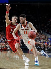 Virginia guard Ty Jerome drives past Texas Tech guard Matt Mooney, left, during the second half in the championship game of the Final Four NCAA college basketball tournament, Monday, April 8, 2019, in Minneapolis.