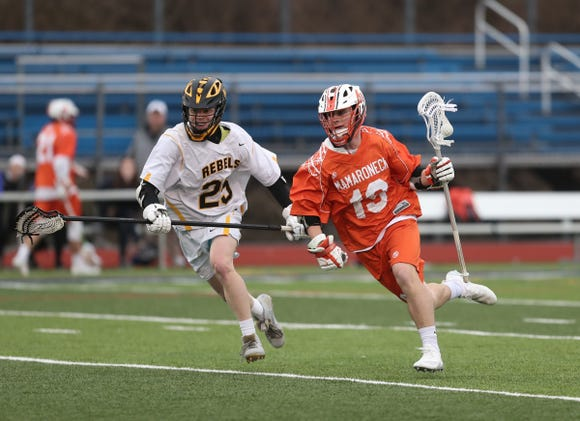 Mamaroneck's JB Connor (19) works past Lakeland/Panas Ryan Brannigan (25) during boys lacrosse action at Walter Panas High School in Cortlandt on Tuesday, April 9, 2019.