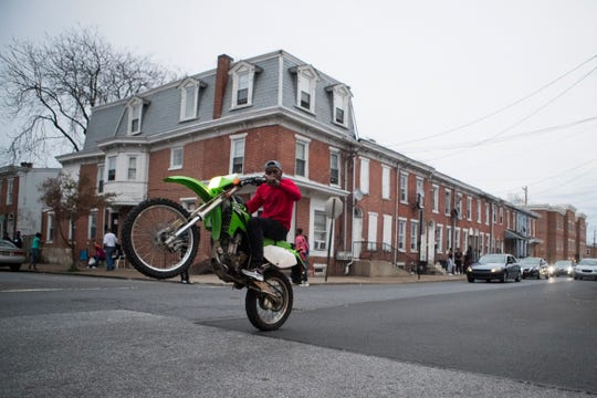 A man pulls a wheelie through the intersection of North Pine Street and East 10th Streets on a spring afternoon in Wilmington.