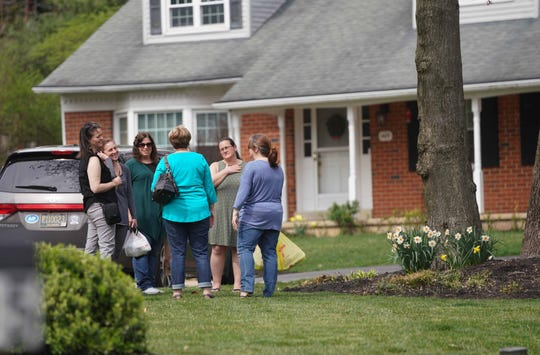 Visitors gather outside of the family home of Staff Sgt. Christopher Slutman, who was a firefighter and father of three killed Monday by an explosion near Bagram Airfield in Afghanistan.