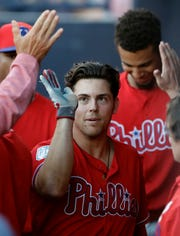 Philadelphia Phillies' Scott Kingery high fives teammates in the dugout after his home run off New York Yankees starting pitcher Jonathan Loaisiga during the third inning of a spring training baseball game Friday, March 22, 2019, in Tampa, Fla.