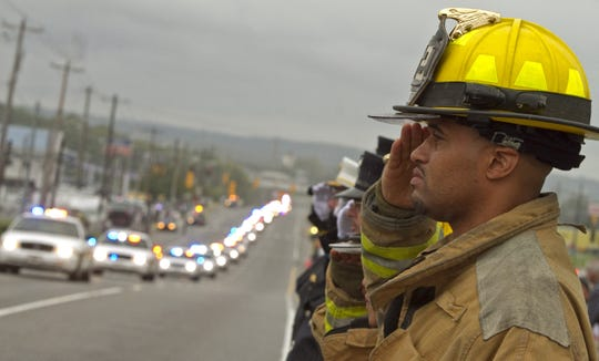 Wilmington Manor firefighter Ty Tucker salutes as the funeral procession carrying the body of Lt. Joseph Szczerba drives by the New Castle County Police headquarters on Sept. 23, 2011.
