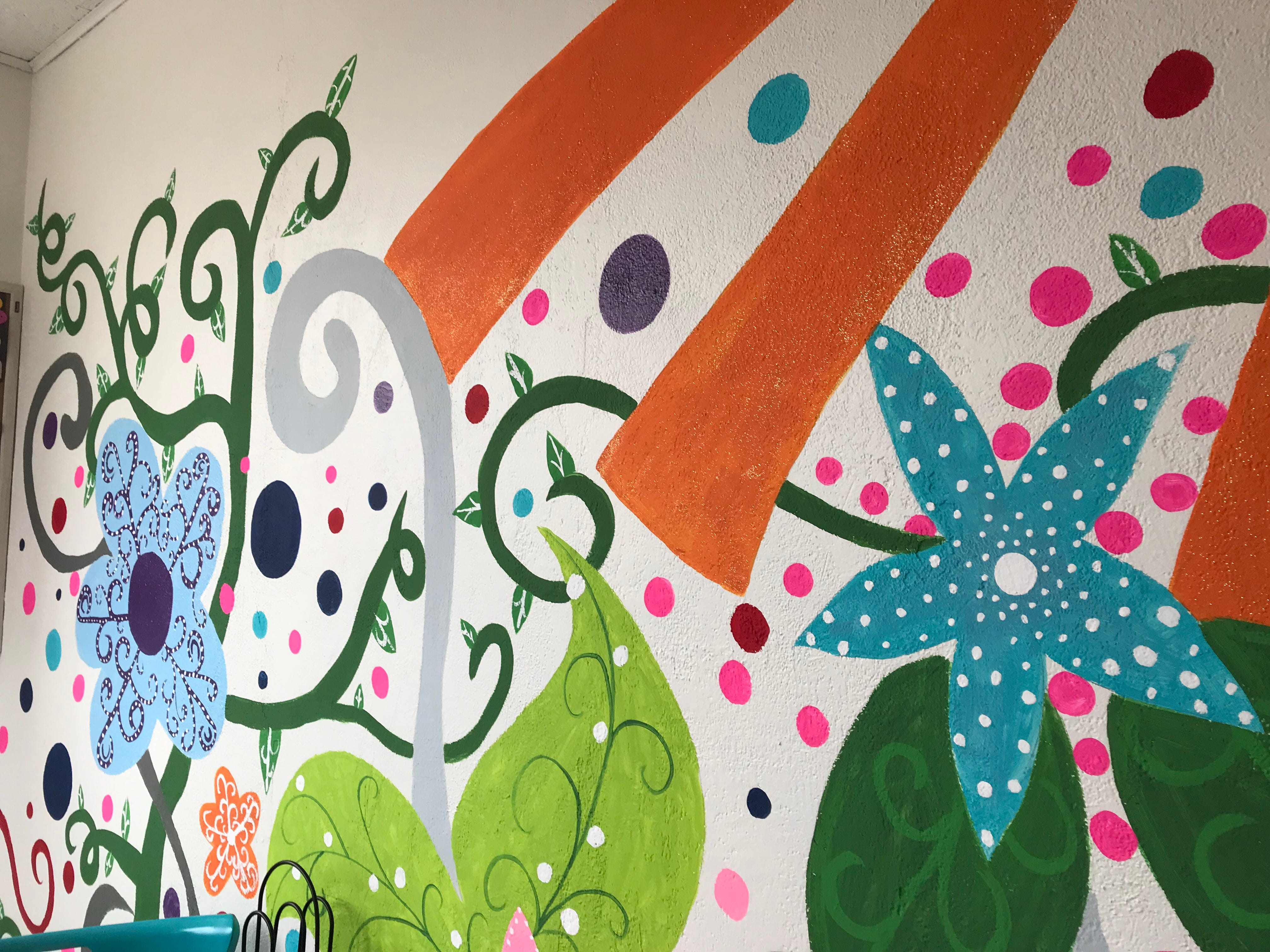 A mural of sun and flowers inside The Sweet Spot in Wisconsin Rapids