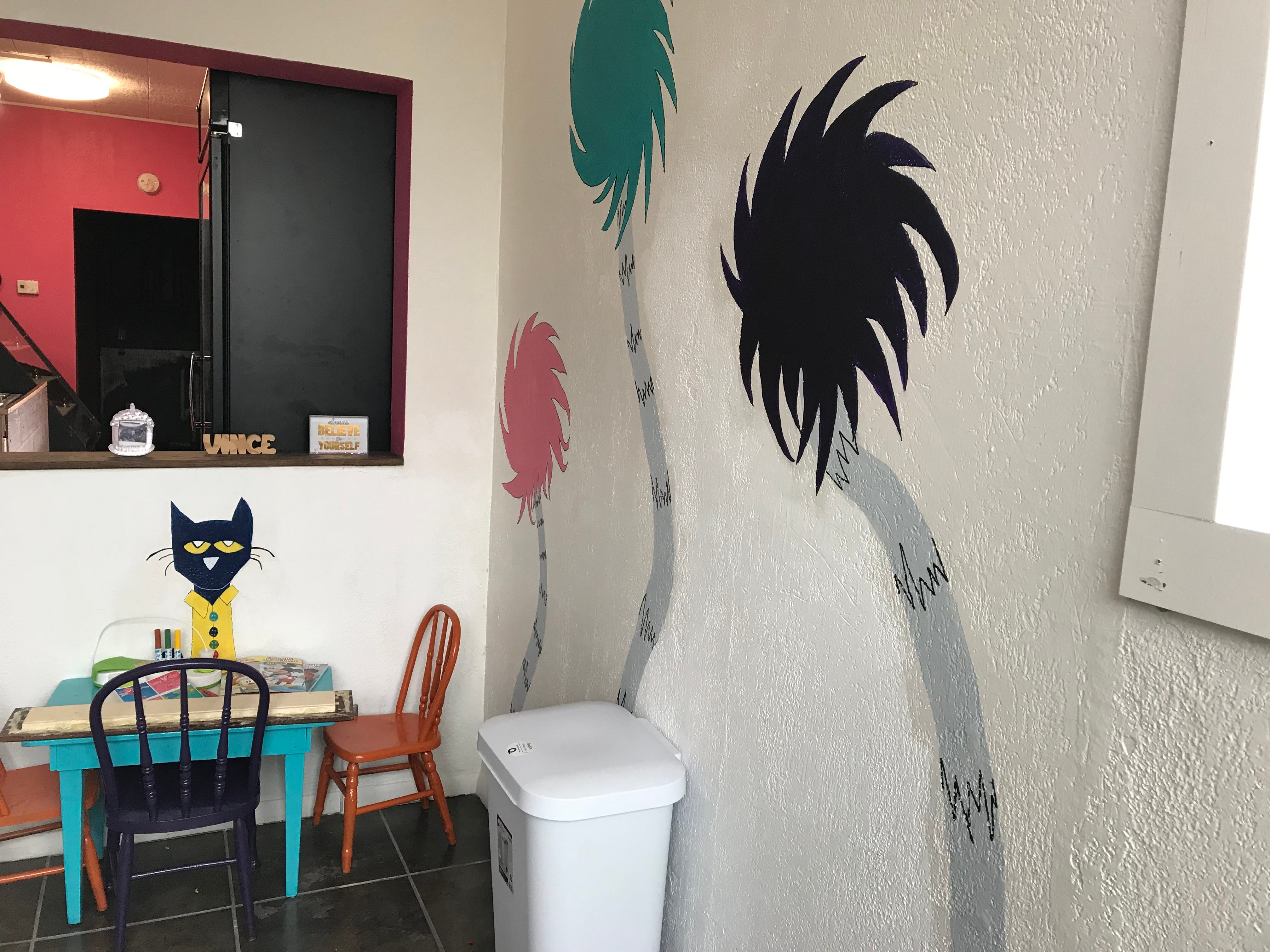Trees and a cat are painted on the walls by a children's table inside The Sweet Spot in Wisconsin Rapids.