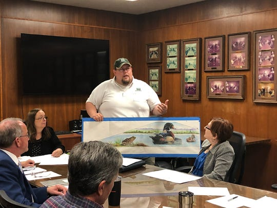 Tom Lang holds an early rendering Tuesday from artist Ralph Stearns for the second mural at the Lake Wichita spillway.