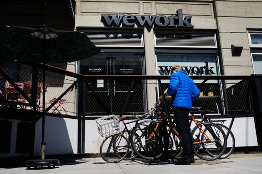 People walk by the co-working space WeWork in the Williamsburg neighborhood in Brooklyn on March 26, 2019 in New York City. WeWork, which lets freelancers and other non-traditional workers to become members in a shared or flexible office space, has expanded globally over the last year.