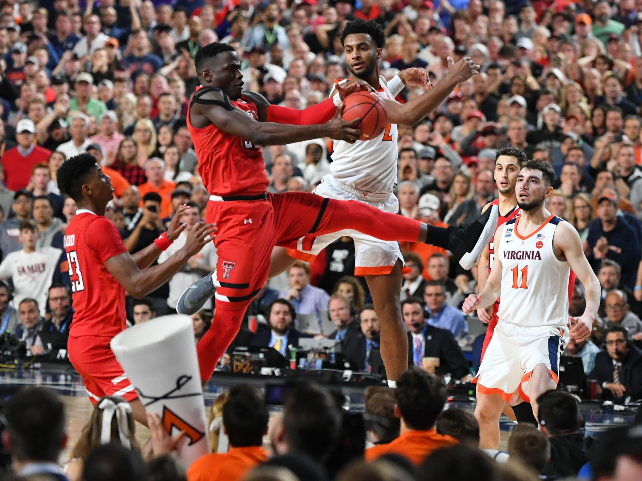 Texas Tech's Norense Odiase battles for a rebound with Virginia's Braxton Key.