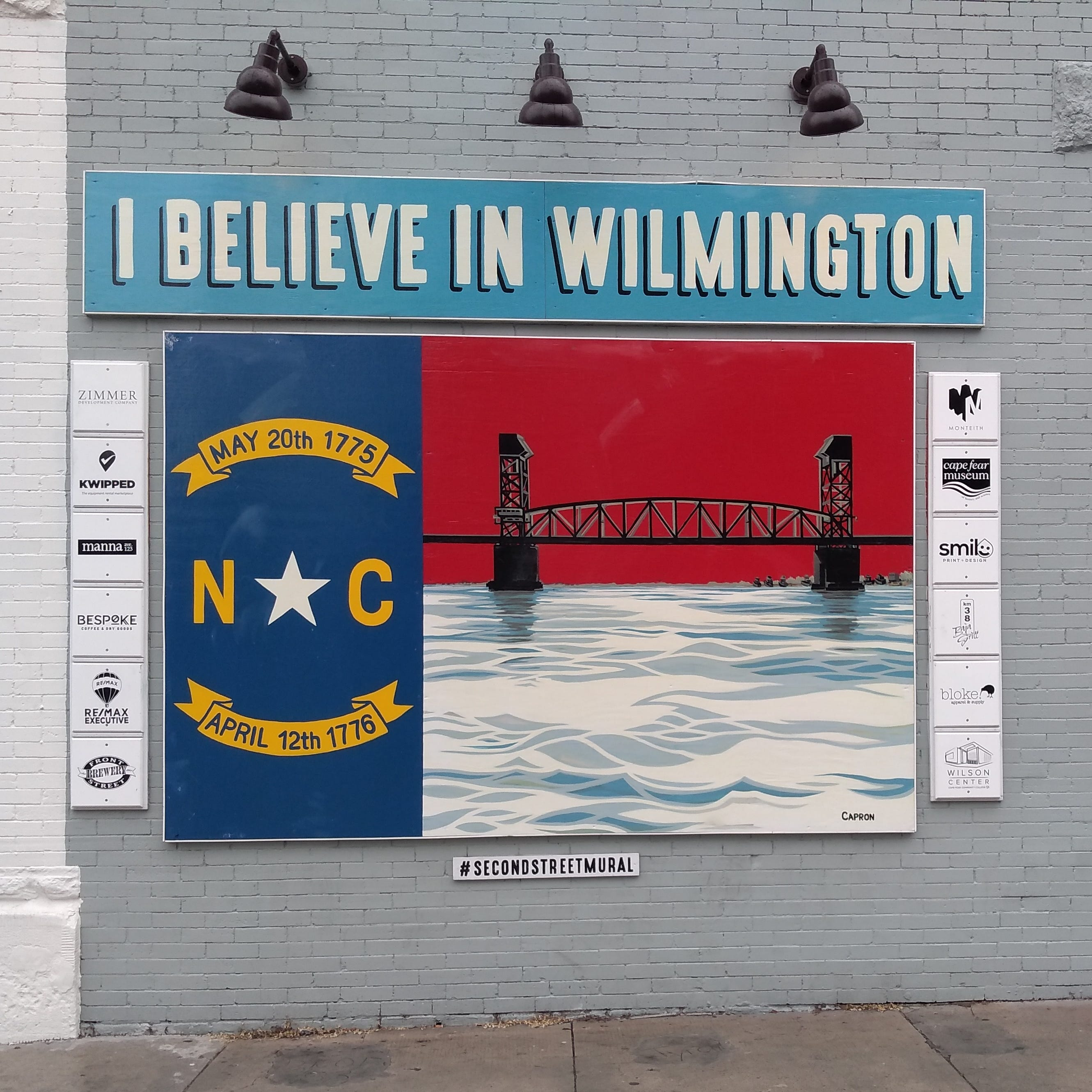 On the side of Manna's building is a mural that's now the iconic photo-op of post-Florence Wilmington. It is a riff on the North Carolina state flag that shows cresting Cape Fear whitecaps just below a silhouette of Wilmington's U.S. 74 bridge.