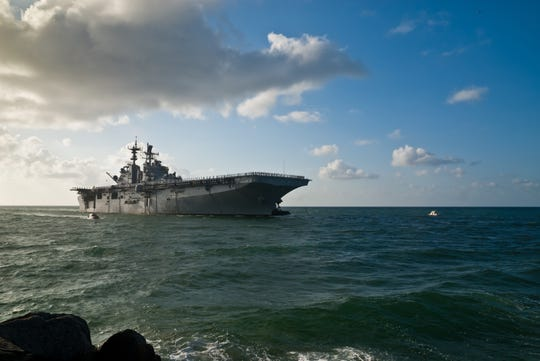 """Morning sun illuminates the USS Iwo Jima (LHD-7) as she sails into Port Everglades in Fort Lauderdale, Florida.  This is a """"big deck"""" amphibious assault ship capable of launching aircraft and watercraft.  Sailors can be seen """"manning the rail"""" as the ship approaches."""