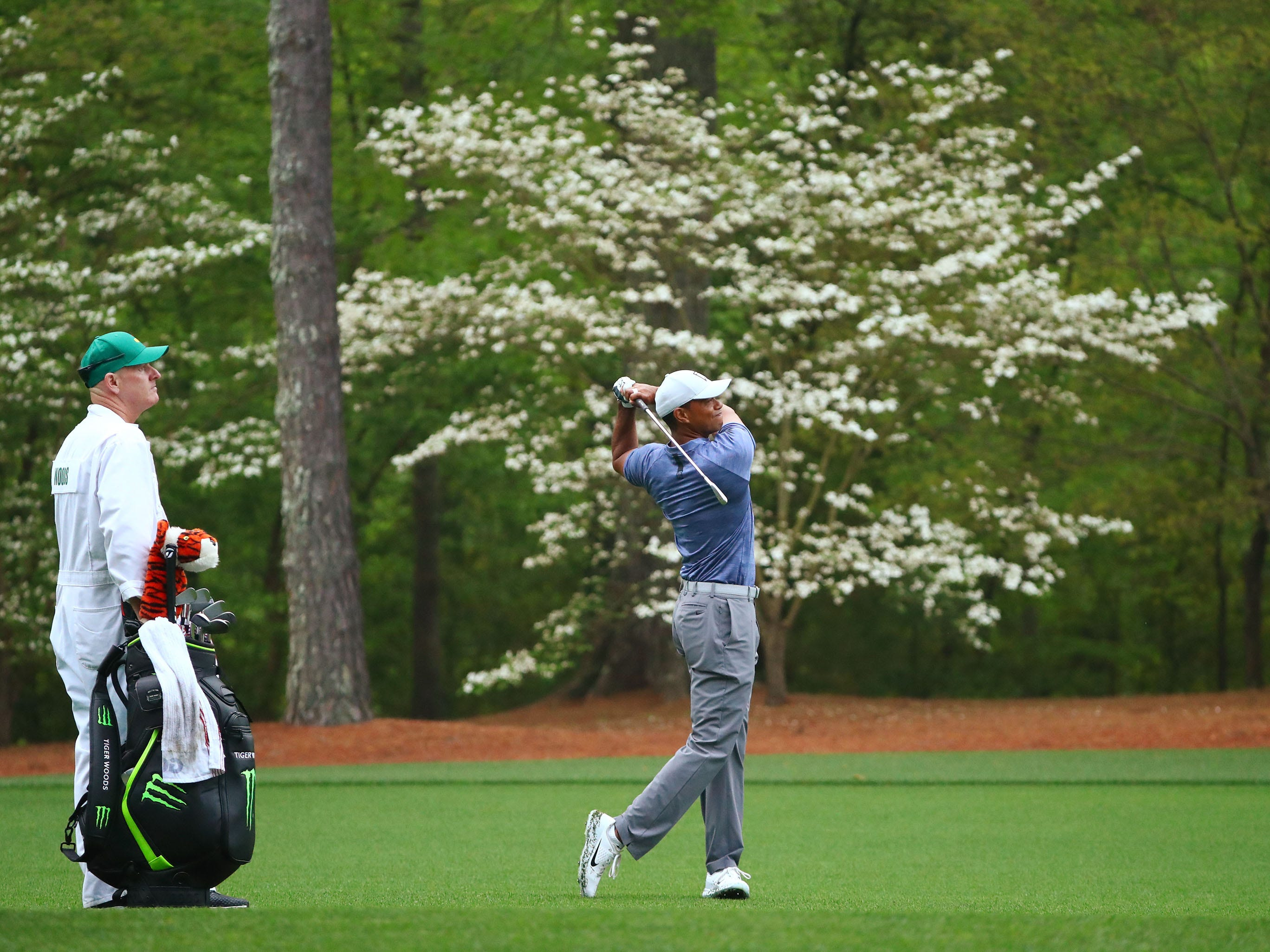 Tiger Woods hits his second shot on the 11th hole during a practice round for the Masters golf tournament.