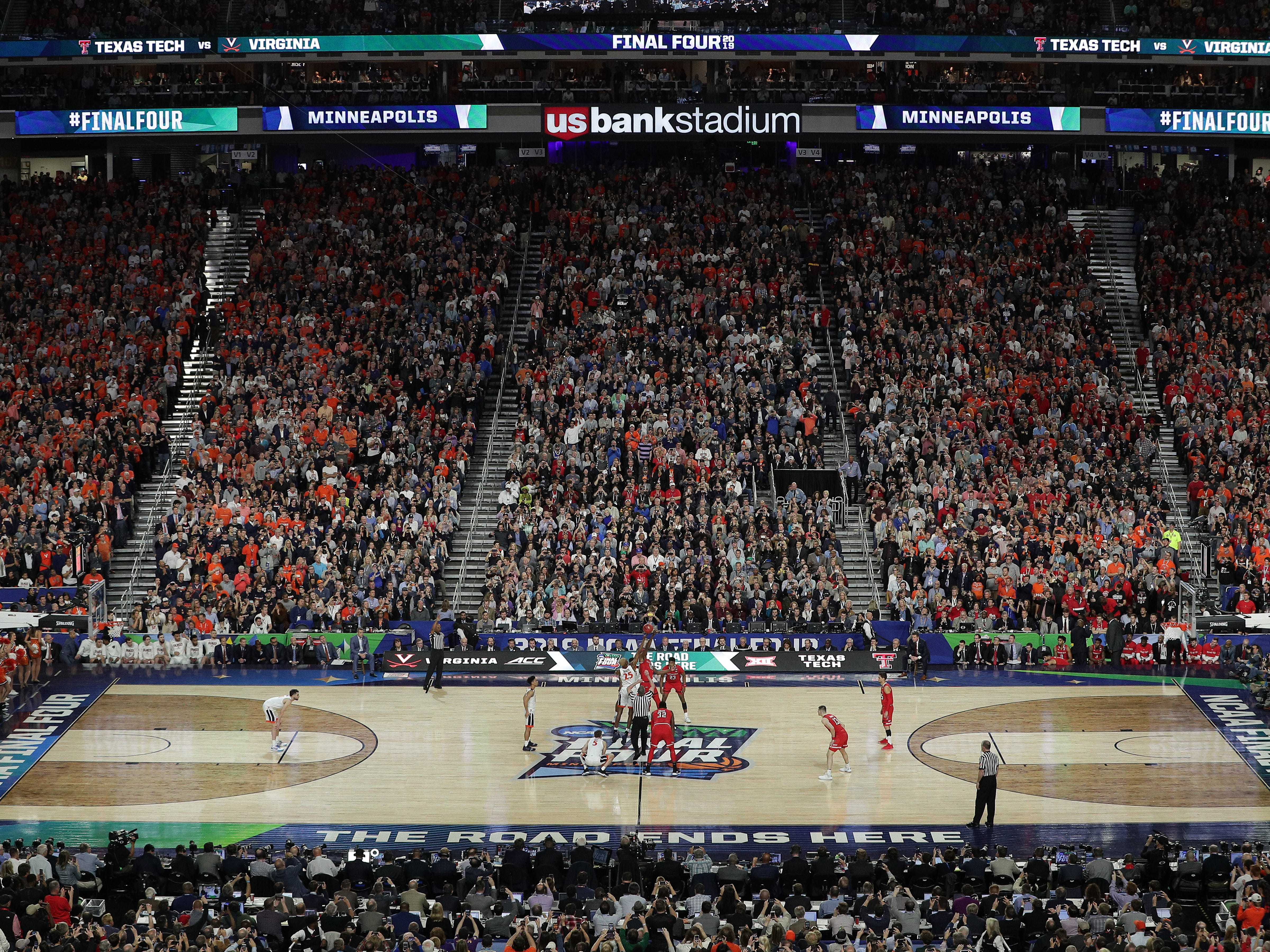 The ball is tipped off in the championship game between Virginia and Texas Tech at US Bank Stadium.