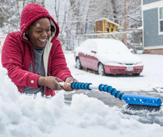 Penza Lemba clears the snow off her vehicle in Lewiston, Maine, on Monday, April 8, 2019, as snow piled up overnight. While New England digs out from one storm, a blizzard is bearing down on the north-central U.S.