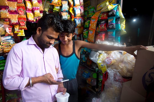 A customer watches election campaign advertisements April 8 on his mobile phone outside a shop in New Delhi, India. From manipulated pictures being picked up by mainstream news media, to misrepresented quotes sparking communal division, false news and hateful propaganda on digital platforms are at peak levels in the run-up to the Indian general elections