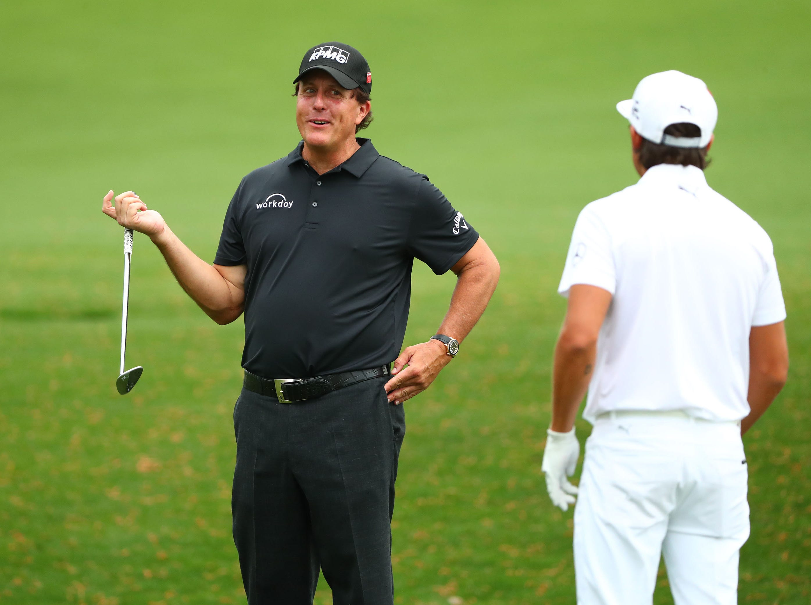 Phil Mickelson and Rickie Fowler (right) talk at the practice facility during a practice round for the Masters golf tournament at Augusta National Golf Club.
