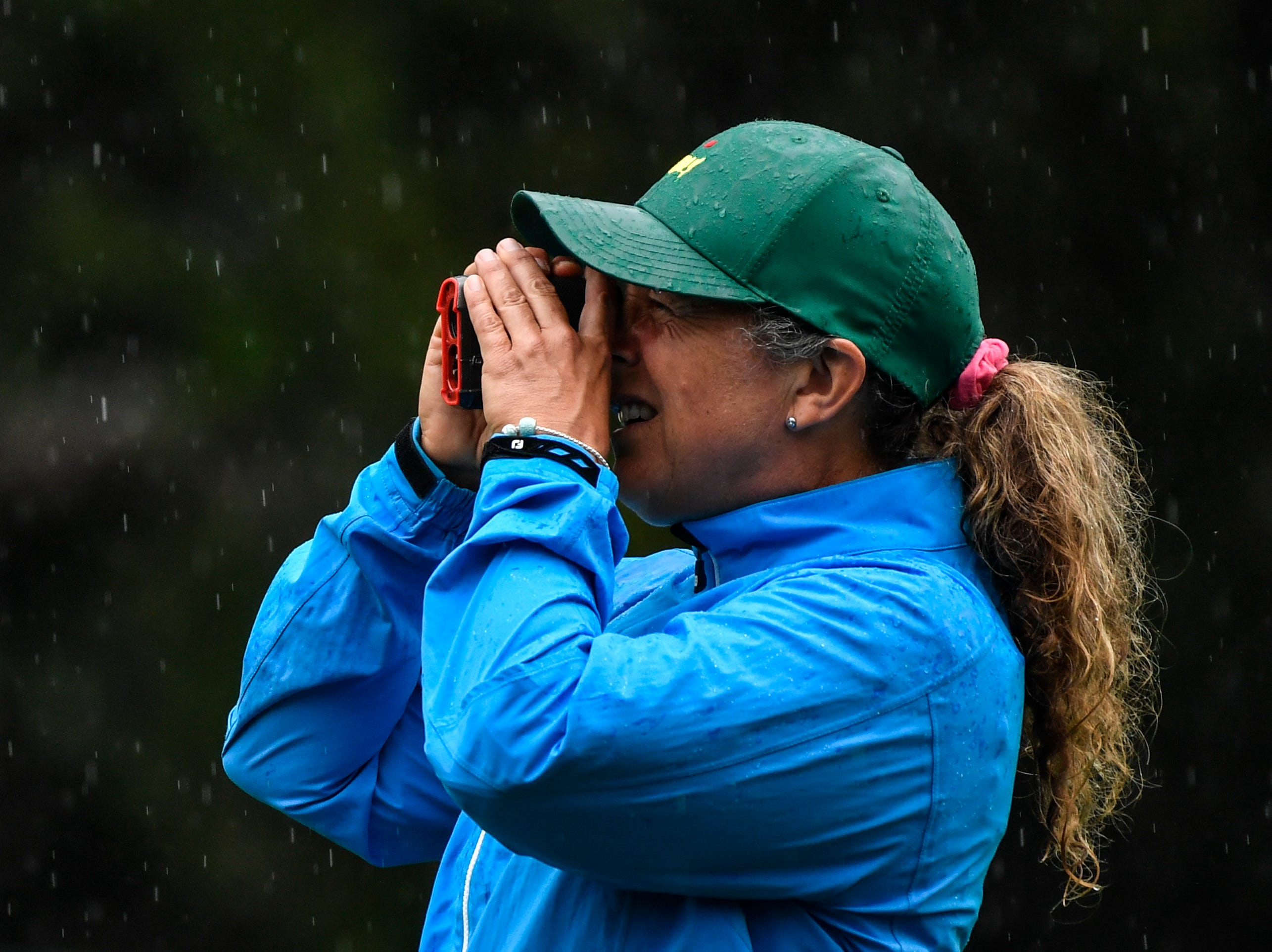 Fanny Sunesson, who is caddying for Henrik Stenson, checks yardage on the first fiarway during a practice round for The Masters golf tournament at Augusta National Golf Club.